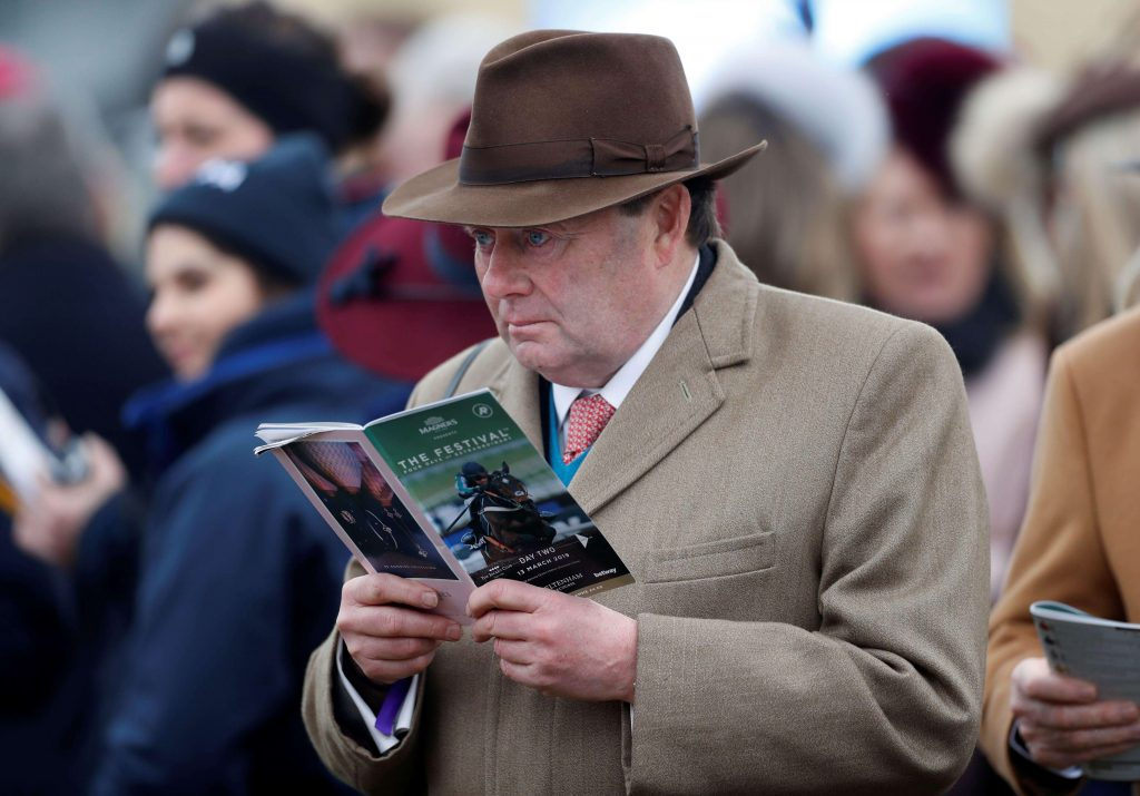 Nicky Henderson reading a racecard at the Cheltenham Festival at Cheltenham Racecourse in Cheltenham, Gloucestershire, England