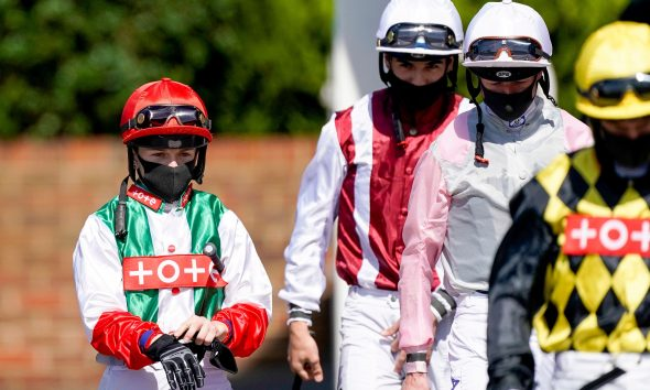 2CEEH7N Jockey Hollie Doyle (left) walks to the parade ring at Kempton Park Racecourse.